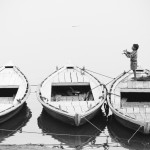 Varanasi, Three boats on the Ganges River, a young boy tries to catch a falling kite. Rendered in a sepia and purple split-tone. Image ©David duChemin